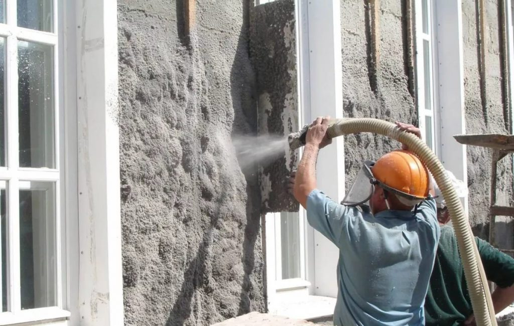 Каркасный дом можно утеплить эковатой, нанесение эковаты на стены дома на фото.